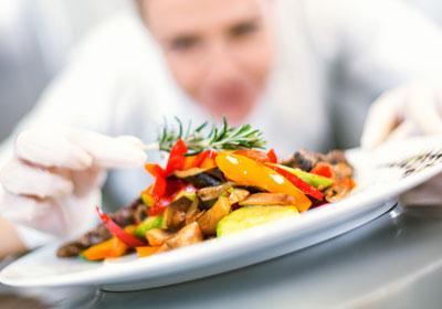 chef adding garnish to plate