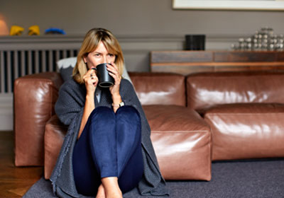 woman sitting on couch with blanket