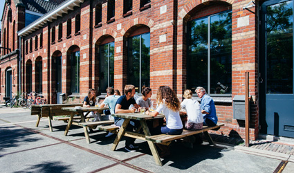 People eating at picnic tables outside brick building restaurant