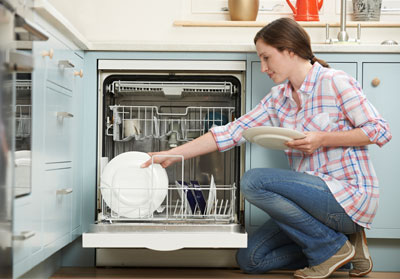 Woman using dishwasher in new kitchen.