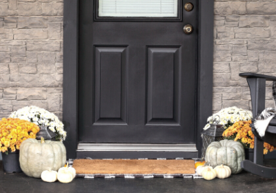 front door with pumpkins and mums