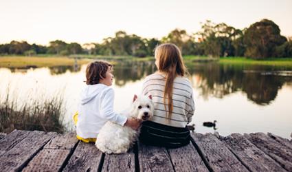 Kids and dog sitting on dock